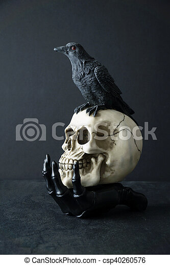 Skull with black bird in skeleton hand - csp40260576