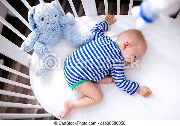 Sleeping baby boy in white crib - csp38580358