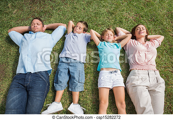 Sleeping family lying on the grass in a row - csp15282272