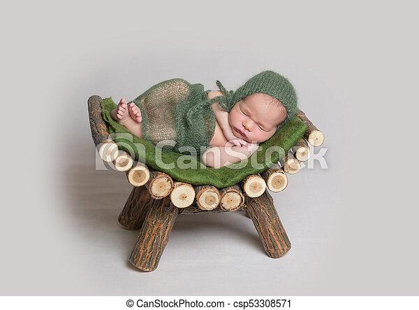 Sleeping newborn baby on wooden crib. - csp53308571