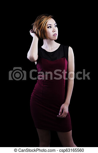 Slender Asian American Woman Standing In Red Dress - csp63165560