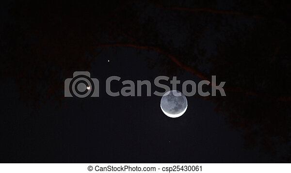 Slender crescent moon with Venus and Jupiter in the western sky at dusk. - csp25430061