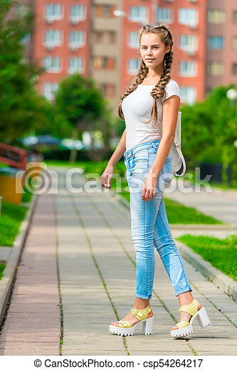 slender girl with a backpack posing on the street - csp54264217