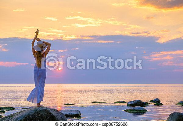 Slender woman in dress enjoying sunset over sea - csp86752628