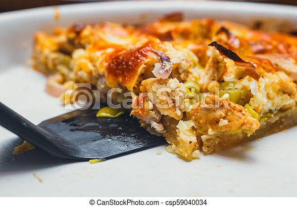 Slice of tart with meat, mushrooms, and cheese on white plate - csp59040034