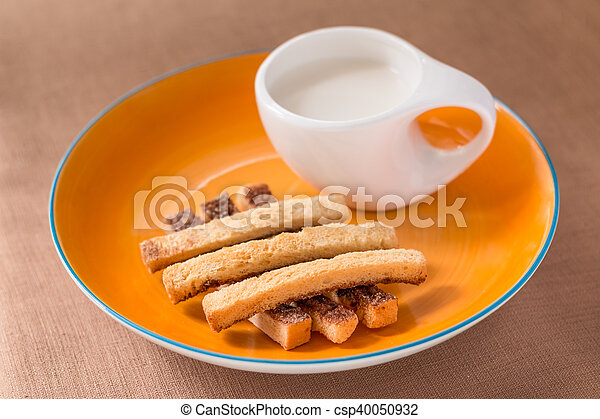 Sliced crispy bread in orange ceramic dish. - csp40050932