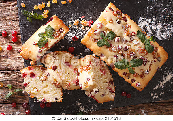 sliced fruit cake with cranberries and raisins decorated with mint close up. horizontal top view - csp42104518