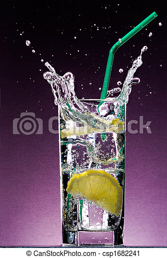 sliced lemon falling in glass of alcoholic drink with ice cubes and green straw on textured violet background - csp1682241