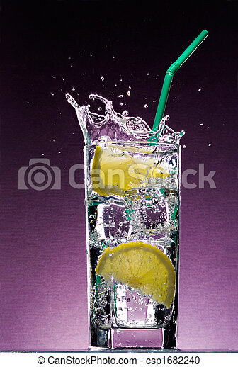 sliced lemon falling in glass of alcoholic drink with ice cubes and green straw on textured violet background - csp1682240