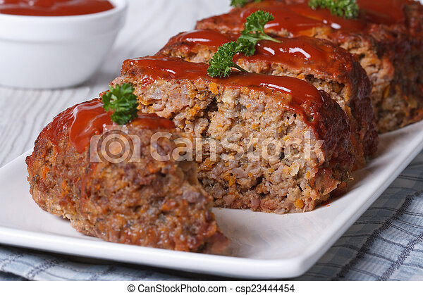 sliced meatloaf with ketchup and parsley horizontal - csp23444454
