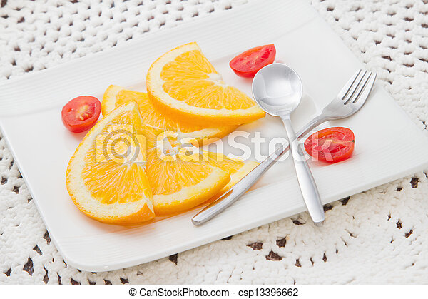 sliced oranges on white plate with red tomato - csp13396662