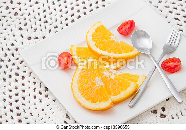sliced oranges on white plate with red tomato - csp13396653