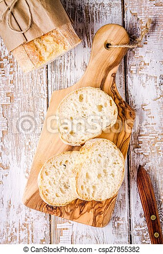 Slices of french Baguette on cutting board - csp27855382