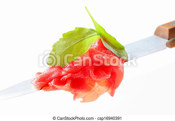 Slices of raw beef on knife - csp16940391