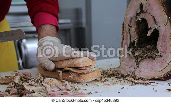 slicing the meat of pork to prepare a sandwich in the food stall - csp45348392