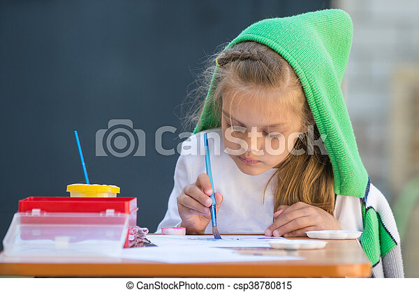 Slightly disheveled girl watercolor paints sitting at the table in the yard - csp38780815
