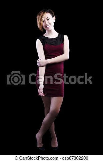 Slim Smiling Asian American Woman Standing In Red Dress - csp67302200