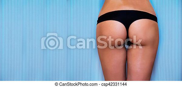 Slim woman in solarium getting sun tan - csp42331144
