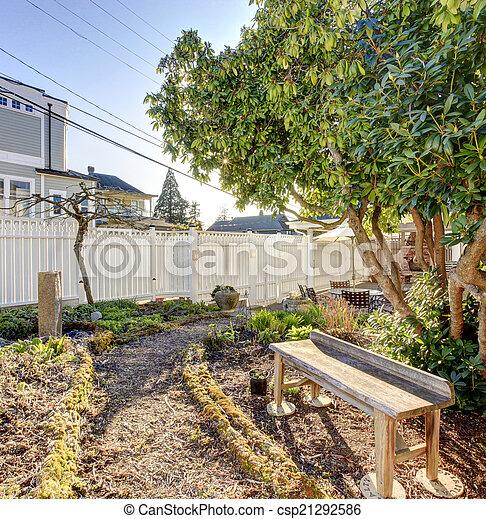 Small backyard garden with wooden bench - csp21292586