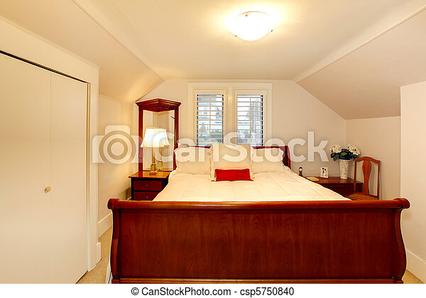 Small bedroom with low ceiling and large bed.