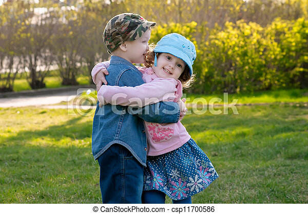 small boy and the girl walk and embrace in park baby walk and
