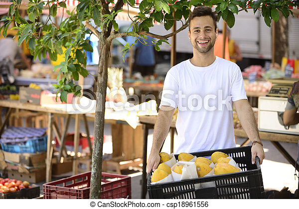 Small business owner selling organic fruits and vegetables at an open street market. - csp18961556