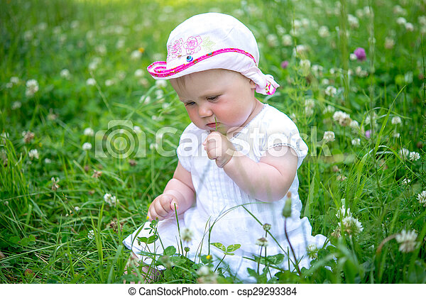 small child sitting in the grass - csp29293384