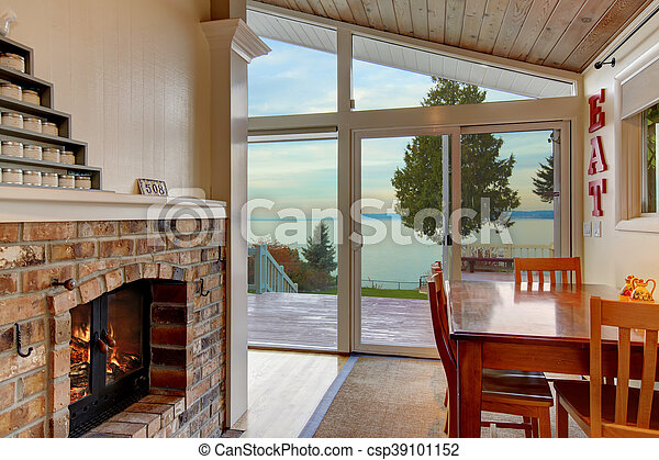Small Dining Area With Brick Fireplace And Water View