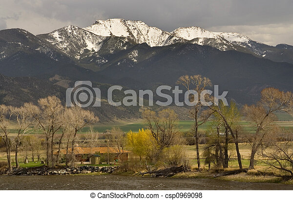 Small Farm by River in front of Snow Mountains - csp0969098