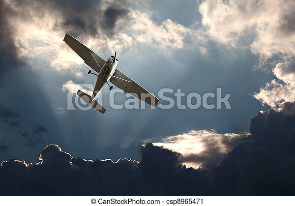 Small fixed wing plane against a stormy sky - csp8965471