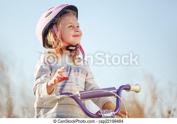 7962e1aee5b7 Small funny kid riding bike with training wheels.