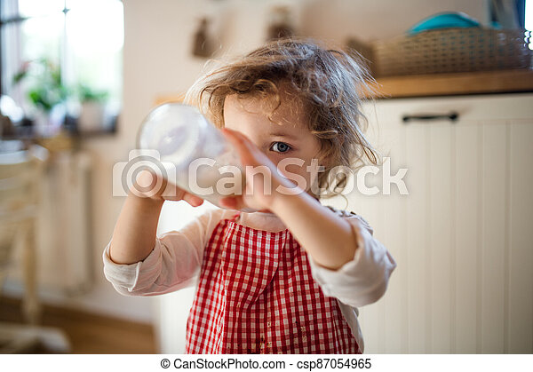 Small girl indoors in kitchen at home, drinking milk from bottle. - csp87054965