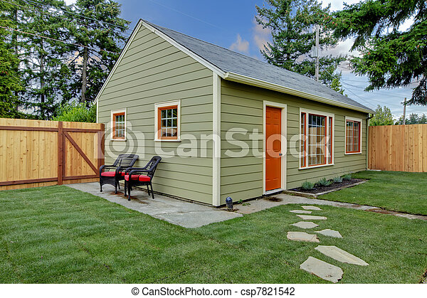 Small green and orange guest house in the back yard - csp7821542