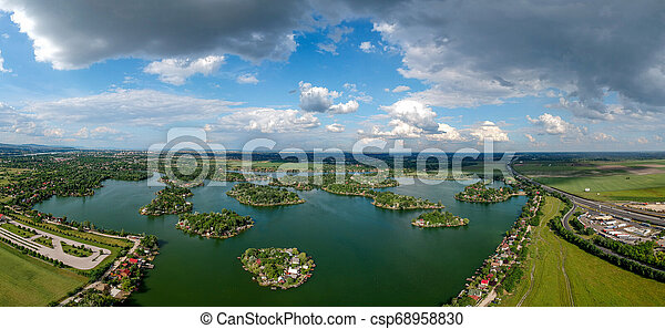Small green islands on a peaceful lake - csp68958830