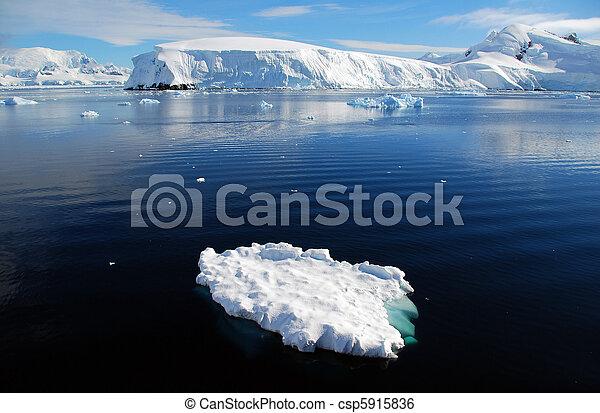small iceberg in front of frozen antarctic landscape - csp5915836