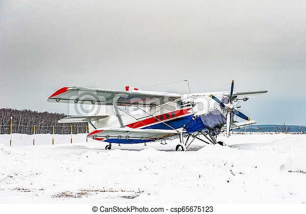 Small plane landed at the airport in winter. - csp65675123