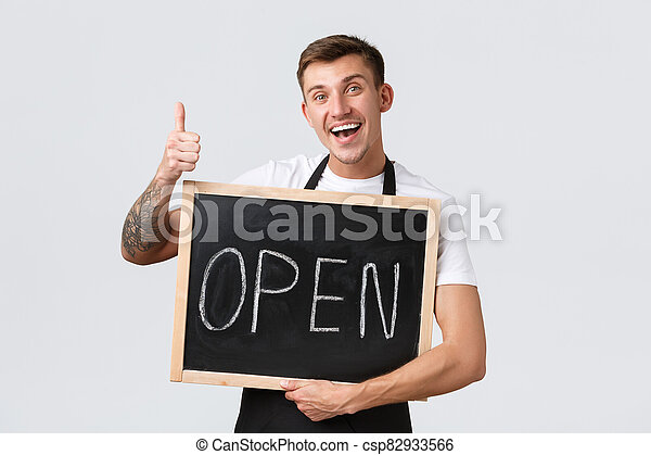 Small retail business owners, cafe and restaurant employees concept. Friendly happy smiling barista, waiter or salesman showing open sign and thumbs-up, inviting to visit store, white background - csp82933566