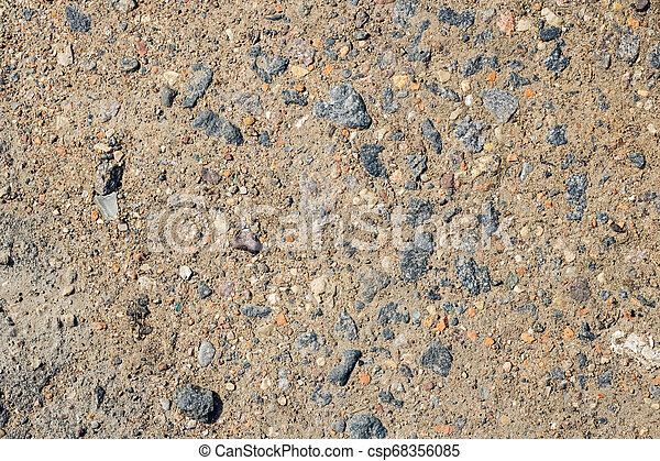 Small stones on yellow sand close up - csp68356085