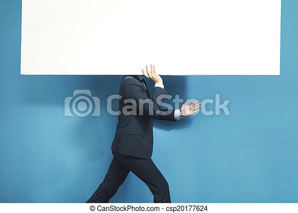 Smart businessman carrying huge board - csp20177624