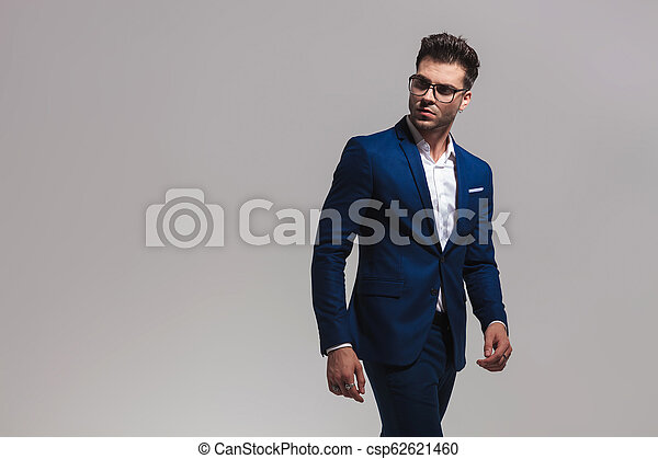 5cce03df89 Smart casual man walks and looks back over his shoulder on grey ...