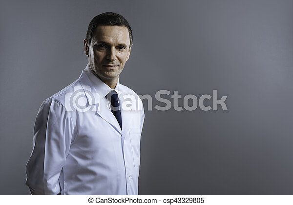 Smart doctor looking serious on a grey background - csp43329805