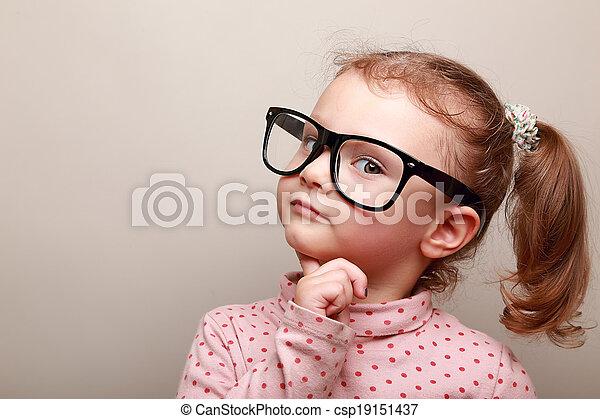 Smart dreaming kid girl in glasses looking - csp19151437
