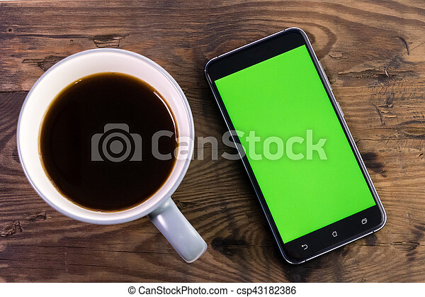 Smart phone with green screen next to coffee cup - csp43182386