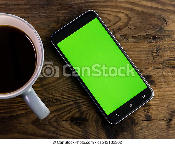 Smart phone with green screen next to coffee cup - csp43182362