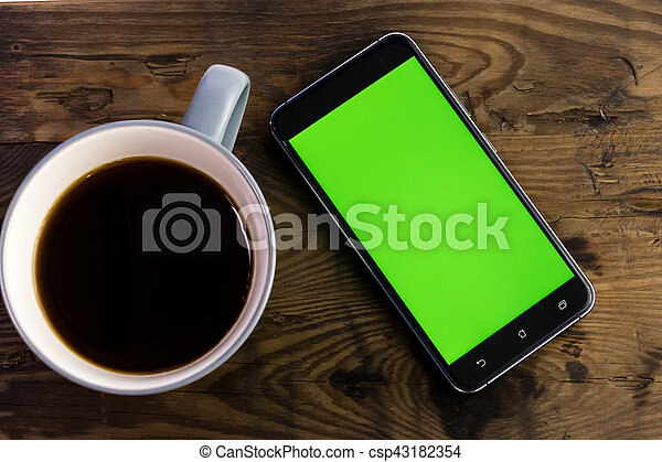 Smart phone with green screen next to coffee cup - csp43182354