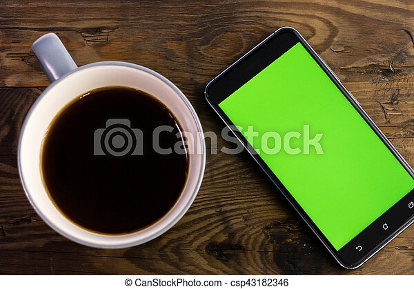 Smart phone with green screen next to coffee cup - csp43182346