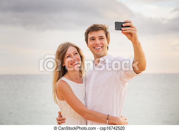 smart, strand, vrouw, liefde, paar, vrolijke , telefoon, man, ondergaande zon , romantische, boeiend, zich, foto - csp16742520