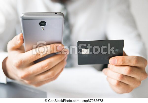Smartphone and Internet Commerce. Online trading on the currency exchange. Online payments through the phone. Payment of goods online. Young businessman with a bank credit card in his hands. - csp67263678