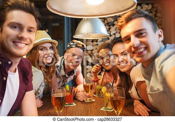Amigos felices con smartphone tomando selfie en el bar - csp28633327