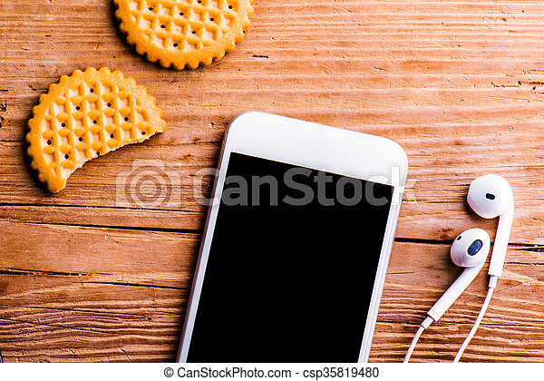 Smartphone, earphones and biscuits laid on old office desk - csp35819480